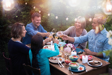 Group of friends in their forties gathered around a table in a garden one summer evening to share a meal. They toast with their glasses of wine