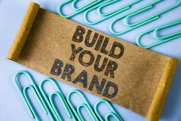 Text sign showing Build Your Brand. Conceptual photo create your own logo slogan Model Advertising E Marketing written on Folded Cardboard paper piece on plain blue background within Paper Pins.