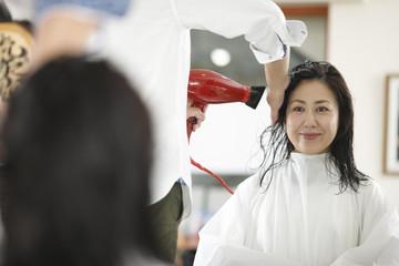美容院でスタイリング中の女性