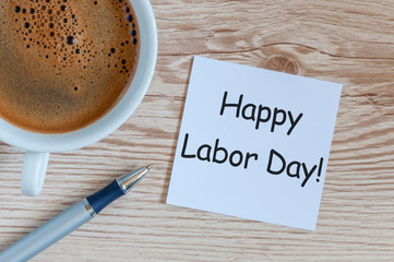 Happy labor Day - message on wooden table background with morning coffee mug. Labour day celebrated at May 1. Spring time