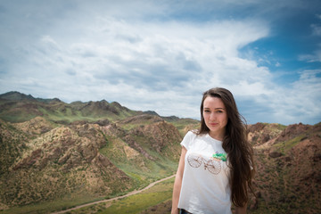 Young woman stands on background with view on the mountains and hills with long country road. Cloudy blue sky.