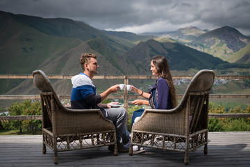 Young couple in good mood sits on the terrace with cups of coffee in morning with beautiful view on mountains. Pretty girl with boyfriend having breakfast.