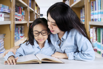 Little girl with teacher sitting in the library