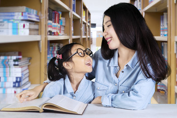 Little girl talking with teacher in the library
