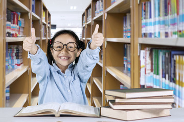 Cute schoolgirl showing thumbs up in the library