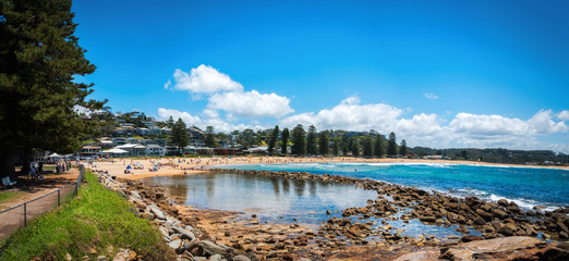 People enjoying a beautiful sunny day at Avoca Beach on the Central Coast, New South Wales, Australia.