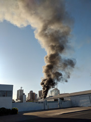 Heavy black smoke plumes from  a warehouse fire in city of Phoenix downtown, Arizona