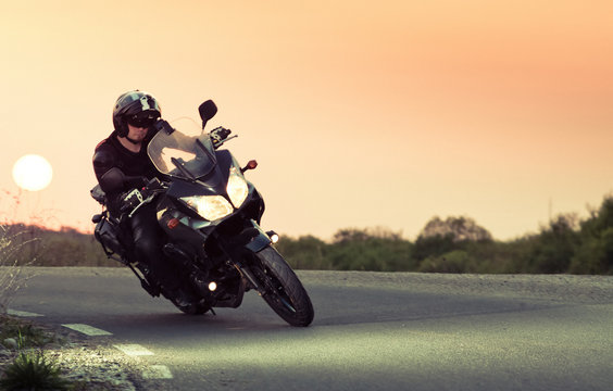 silhouette of rider on a motorbike driving at sunset - space for your text