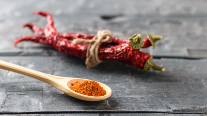 A light wooden spoon with ground pepper and a bunch of chili pods on the rustic table.