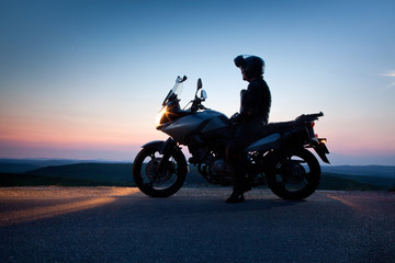 man on his motorbike admiring sunset - summer road trip - space for text