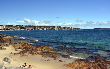 Delwood beach on a sunny day in summer. North Head and South Head are in the background. Sailing boats in Sydney harbour.