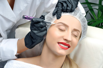 Microblading. Cosmetologist making permanent makeup. Attractive woman getting facial care and tattoo eyebrows