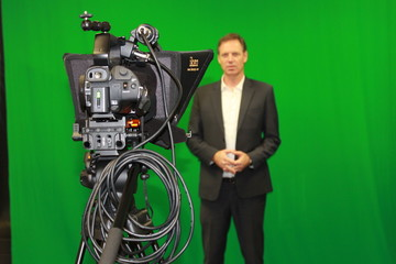 Man reading autocue teleprompter against green screen