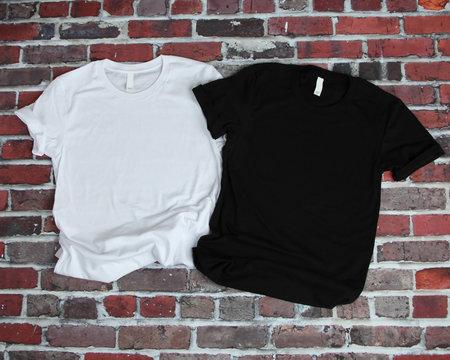 Flat lay mockup of white tshirt and black tshirt on brick background