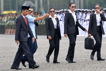 Indonesia President Joko Widodo and Armed Forces Commander Hadi Tjahjanto are escorted by female members of the Paspampre sduring an event marking Kartini Day in Jakarta