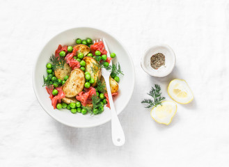 Young baked potato, smoked salmon, green peas and dill salad on light background, top view