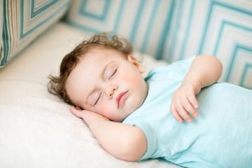 Adorable toddler child boy taking a nap