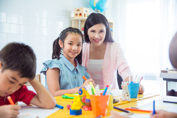 Pretty asian girl and teacher smiling in art classroom