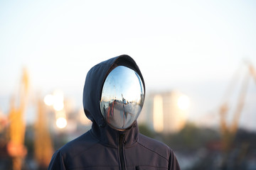 Faceless character with the mirror mask with port in background.