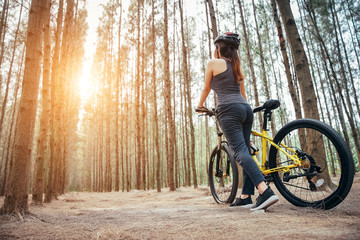 Asian girl is exercising, she waring a helmet and riding a bicycle at the weekend in a pine forest green. Sport girl and lifestyle concept.