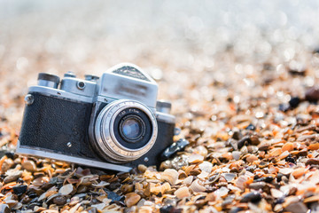 Retro photo camera on the beach. Close-up photo. Vacation concept