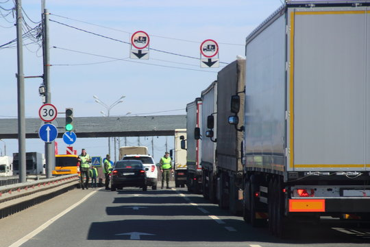 The queue of trucks with semi-trailers to the control point in the spring against the blue sky, inspectors in yellow jackets and camouflage check the documents of the driver of the car