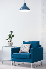 Modern lamp with plant on table and armchair indoors