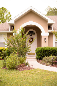 Front door with arc Florida style home. tan color with tree out front. front door deliver.