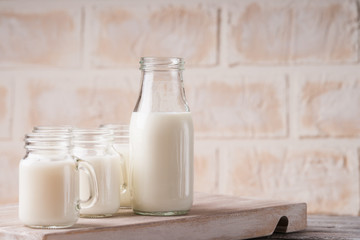 Jars and bottle with milk on a cutting board