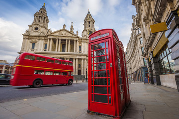 London, England - Traditional red telephone box with iconic red vintage double-decker bus on the move at St.Paul's Cathedral on a sunny day