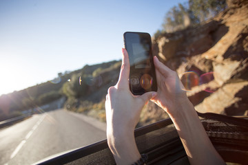 Close up of woman holding out smartphone from car window or roof skylight of convertible to make photo or video of road ahead, concept summer adventures and travel blogger