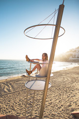 Social media blogger influencer, young woman or teenager in fashionable outfit stands on top of lifeguard tower on empty california beach, poses for photoshoot for fashion blog, awesome lifestyle