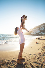 Young happy woman or teenager, proud dog owner holds her best friend little beagle puppy in her arms up in sky, in amazing sunset on empty beach, concept happiness and pet love to animals