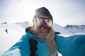 Cool, beautiful, young and attractive teenager or active lifestyle woman makes photo selfie on smartphone or action camera on ski slopes when snowboarding in mountains, wears goggles for snow and sun