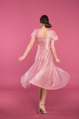 girl is spinning in a dress. designer dress from pink satin on a pink background