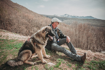 man and his dog sitting looking the mountains
