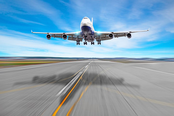 Poster Avion à Moteur Passenger airplane four engine with a cast shadow on the asphalt landing on a runway airport.