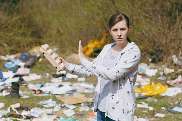 Upset woman in casual clothes cleaning holding rubbish and showing stop gesture with palm in littered park. Problem of environmental pollution. Stop nature garbage, environment protection concept.