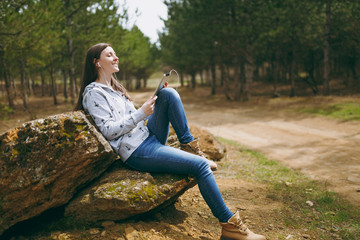 Young relaxing smiling woman in casual clothes sitting on stone listening music with earphones and tablet pc computer in city park or forest on green background. Student lifestyle, leisure concept.