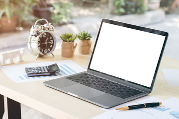 Blank white laptop screen display on wooden table with business document, pen calculator, clock and small flower pots in office.
