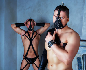 two muscular striptease dancers wearing leather costumes