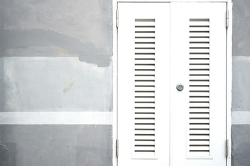 Closed and locked white entrance door on grey painted cement wall background.