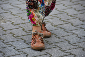 Woman's legs with colorful trousers and shoes with shoelaces
