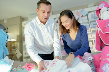 Man and woman looking at linen for baby girl