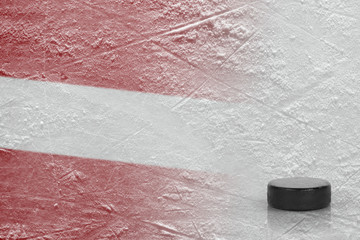 Image of the Latvian flag with a hockey puck
