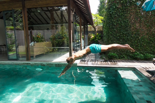 side view of tattooed man diving into swimming pool during vacation on bali, indonesia