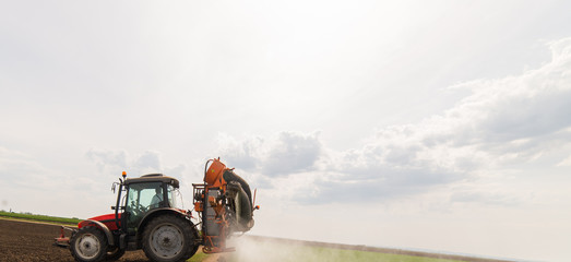 Fotomurales - Tractor spraying pesticides on wheat field with sprayer at spring