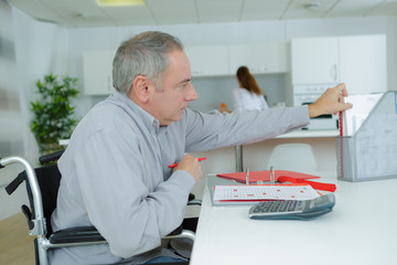 handicapped accountant reaching for a file