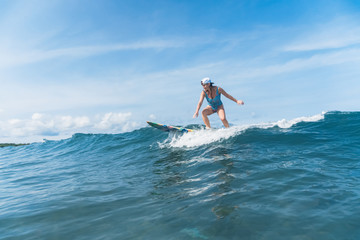 woman in swimming suit surfing in ocean