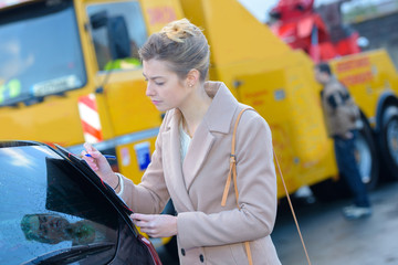woman filling car tow papers